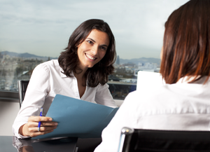 Two women in business attire sit at a desk; one holds a blue file folder.
